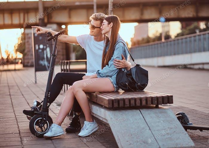 Beautiful couple are enjoying sunset on the bench