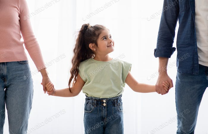 Adoption Concept. Adorable Little Girl Holding Hands With Unrecognizable Mom And Dad