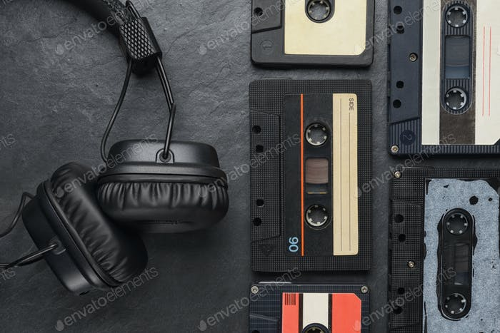 Headphones and compact cassettes on black slate background