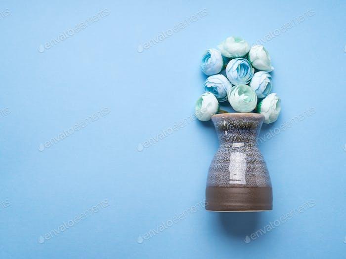 Vase with decorative flowers on blue background