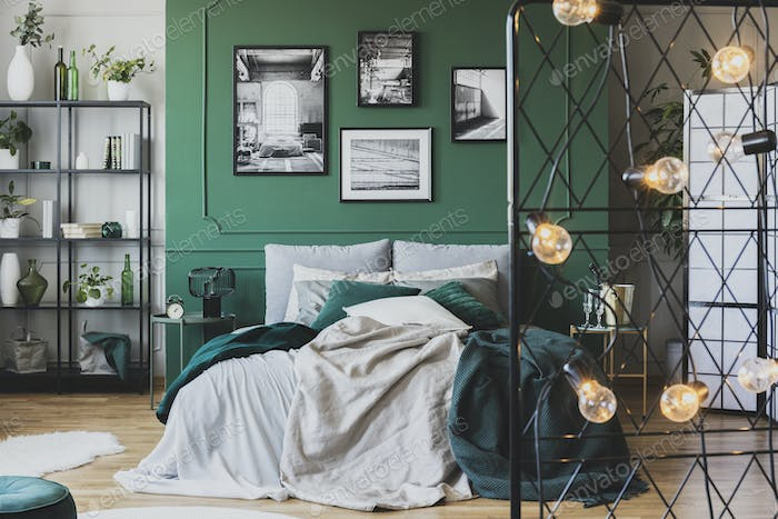 Cozy bed with pillows and blankets in emerald and grey colors