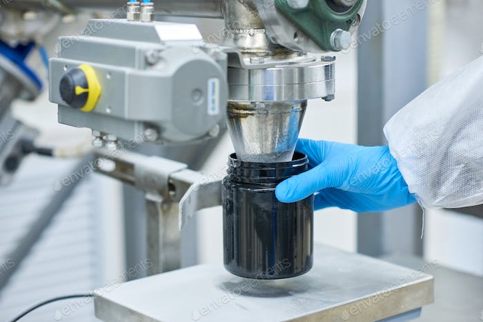 Factory worker filling plastic jar with product