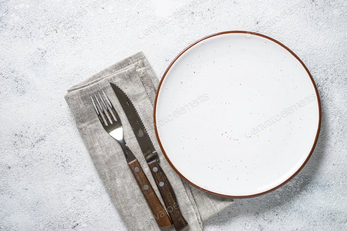 White plate and cutlery on stone table top view