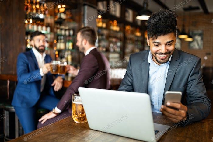 La gente de negocios bebe cerveza después del trabajo. Los hombres de negocios disfrutan de una cerveza