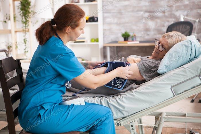 Female nurse in nursing home doing blood pressure measurement of a senior woman patient