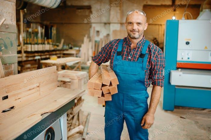 Zimmermann hält Stapel von Holzbalken, Zimmerei