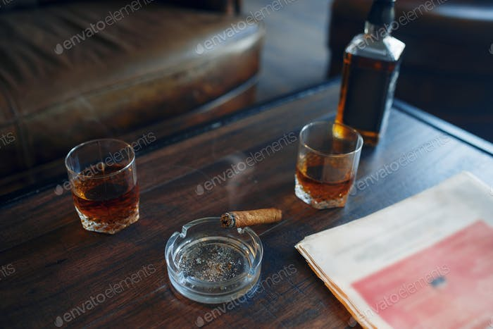 Whiskey and cigar on wooden table in retro office