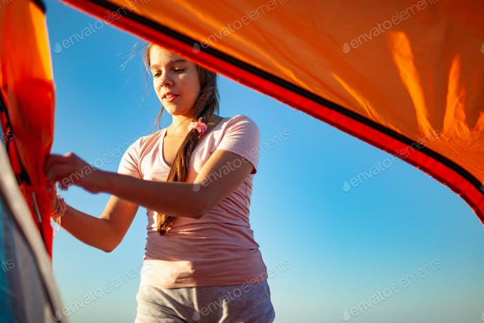 Young girl closes the tent looking at her actions on the blue sea shore