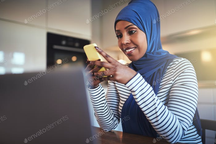 Smiling Arabic entrepreneur sitting in her kitchen sending text messages