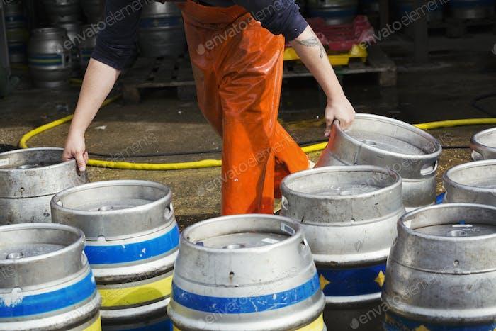 Man working in a brewery, holding metal beer kegs.