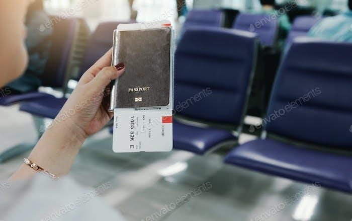 Frau Hand hält Reisepass und Flugticket am Flughafen.