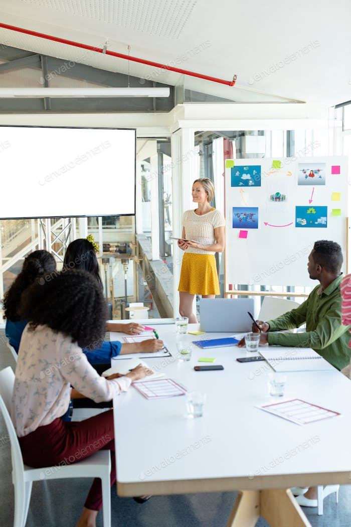 Front view of diverse businesswoman giving presentation on screen during meeting in a modern office