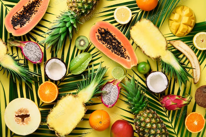 Exotic fruits and tropical palm leaves on pastel yellow background - papaya, mango, pineapple