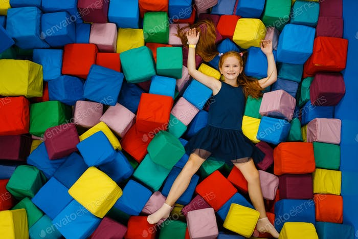Cute little girl lying in soft cubes, playground