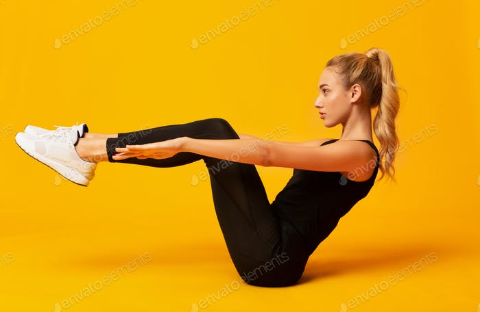 Girl Doing Abs Exercise With Leg Raise On Yellow Background