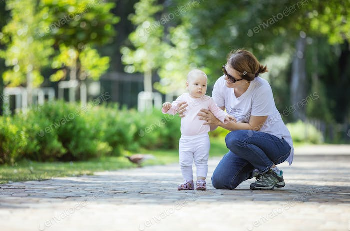 Mother supporting baby daughter and helping her make first steps