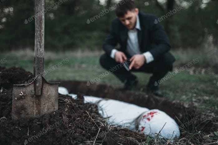 Jägerin gegen Grab, Opfer in eine Leinwand eingewickelt