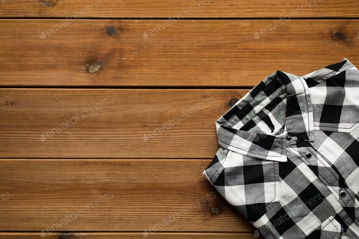close up of checkered shirt on wooden background