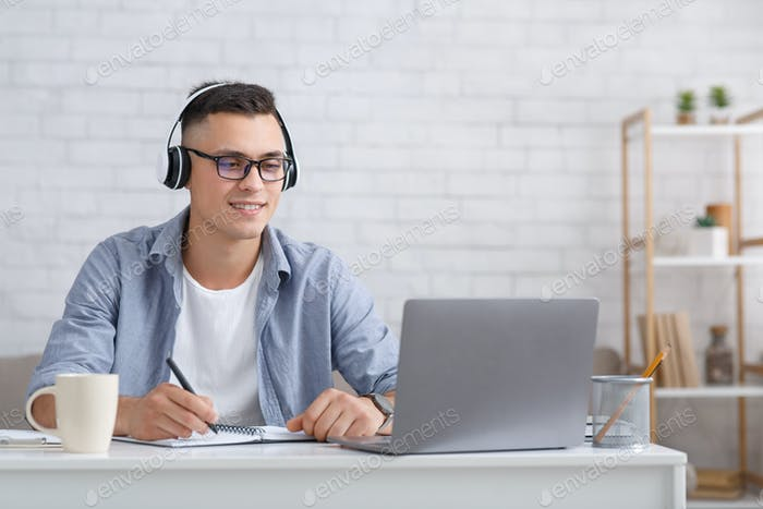 Online webinar or lesson during covid-19. Attractive guy in glasses and headphones looks at laptop