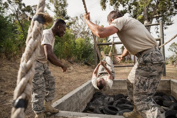 Thumbnail for Young military soldiers practicing rope climbing during obstacle course