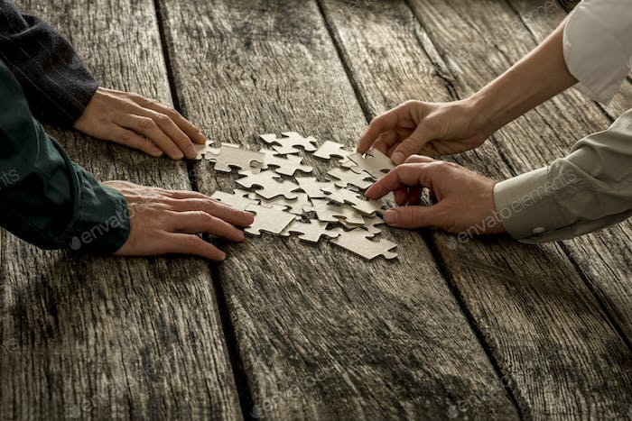 Pile of puzzle pieces lying on wooden desk with four hands reach