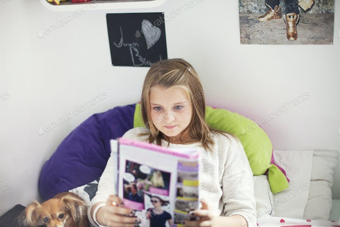 Girl reading novel while lying on bed at home