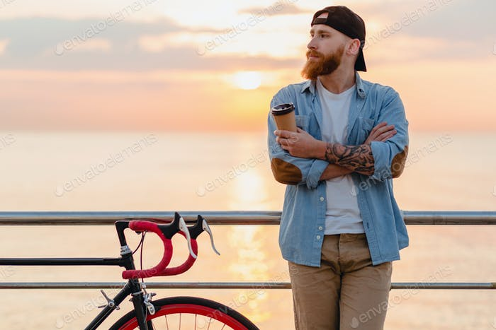 handsome bearded man traveling with bicycle in morning sunrise by the sea