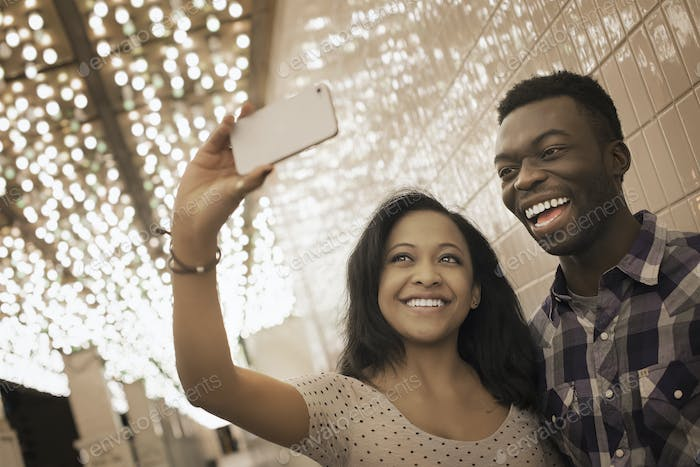A man and woman in a brightly lit space, a casino entrance, taking a selfy with a smart phone.