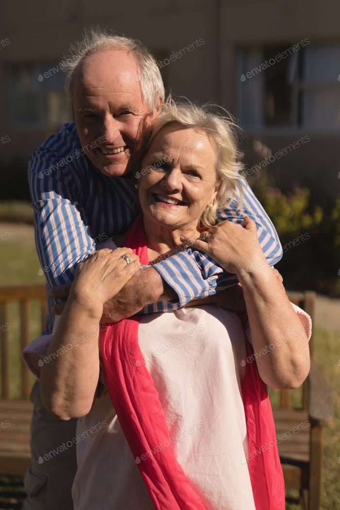 Portrait of active senior Caucasian couple embracing each other in the park
