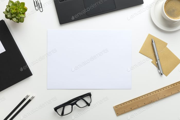 Top view of modern white office desk with notebook and supplies
