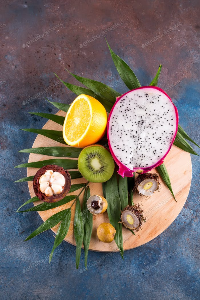 Tropical half fruits assortment on a wooden round play on a stone background pattern. Top view. Copy