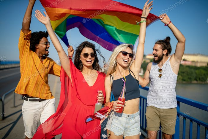 Pride homosexual, lesbian, gay community at a parade with hands raised and the LGBT flag