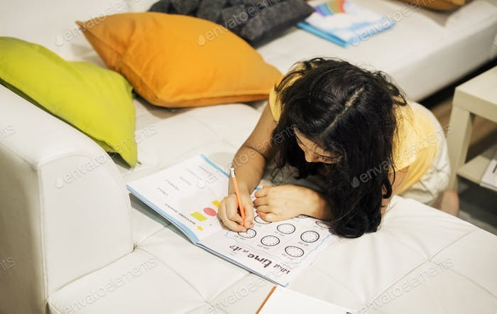 Young brazilian girl working on exercise book on couch