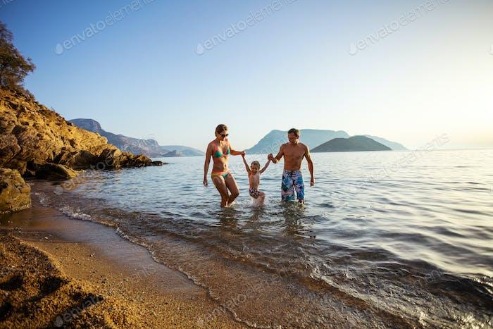 Caucasian family of three having fun on beach