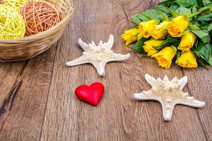 Seesterne, Herz und Rosen auf einem Holztisch