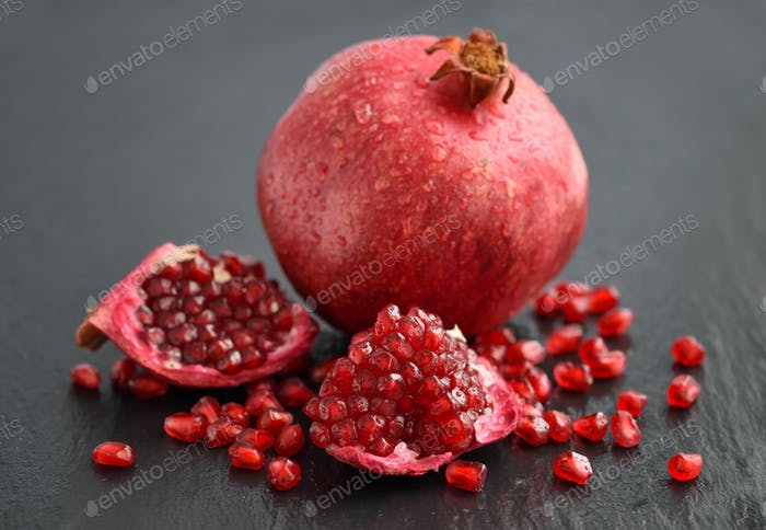 Ripe pomegranate and seeds scattered on black stone background