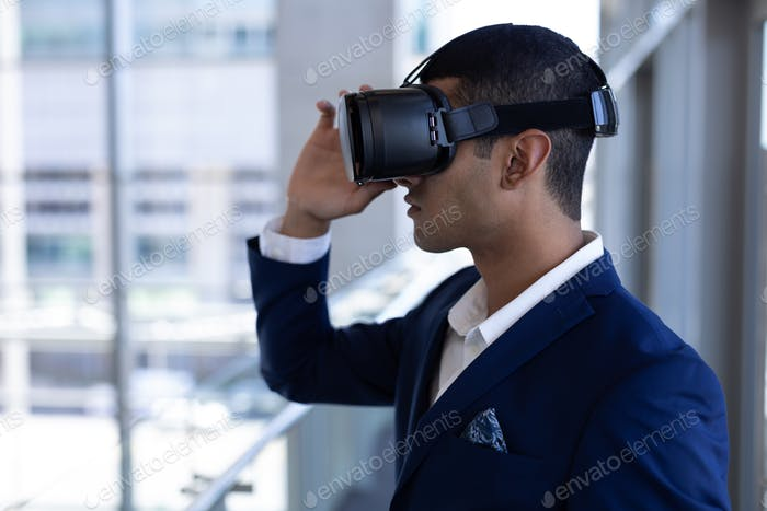 Handsome young mixed-race businessman using virtual reality headset standing in modern office