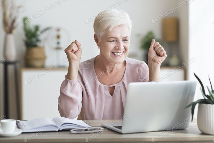 Happy senior woman celebrating success in front of laptop
