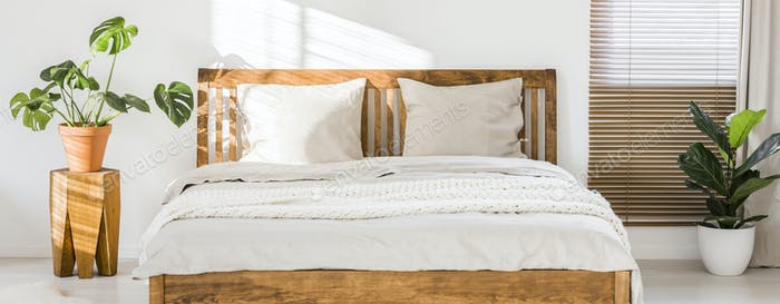 Close-up of double wooden bed with bedding, pillows and blanket