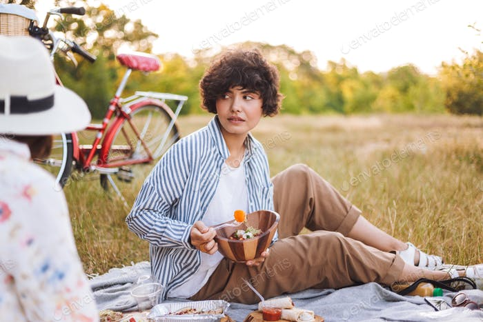 Beautiful girl in striped shirt holding bowl with salad while dr