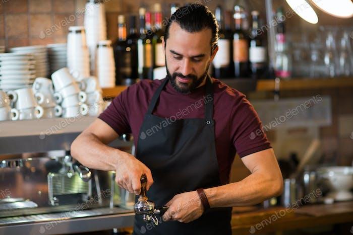 barista man making espresso at bar or coffee shop