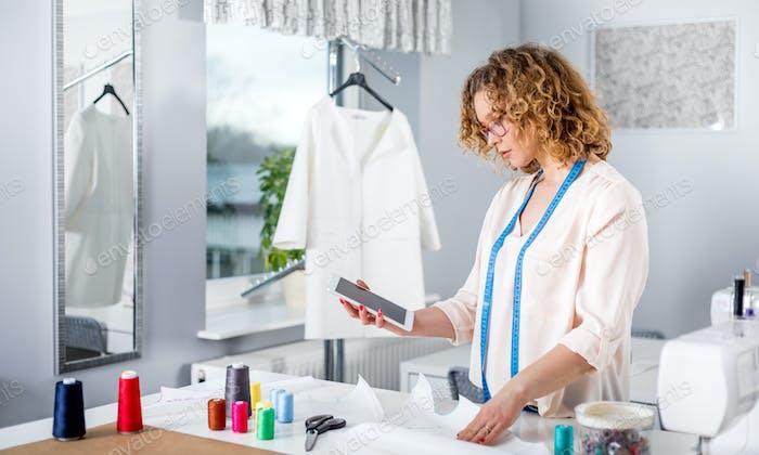 Maßgeschneidert mit digitalem Tablet, moderne Modedesignerin in der Werkstatt