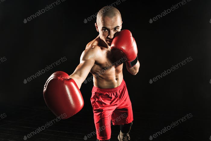 The young man kickboxing on black