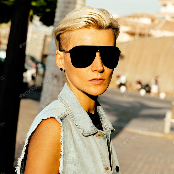 Stylish blonde in trend sunglasses and denim clothes in the city