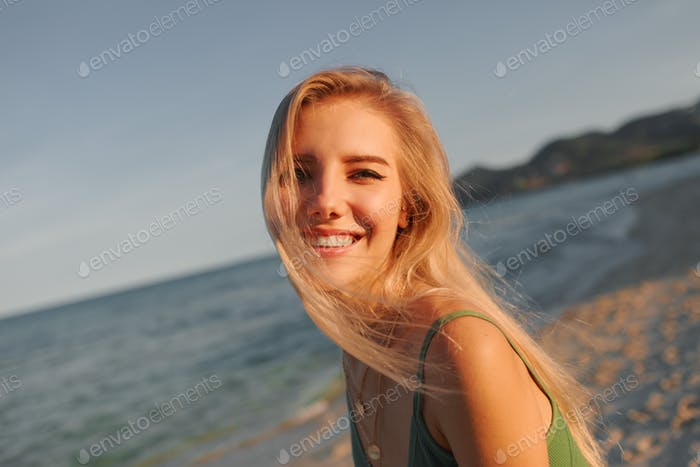 Lovely blond woman having fun on the beach. Summer vacation