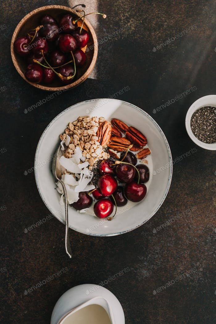 Healthy summer vegetarian breakfast with granola, cherry, pecans, coconut flakes, chia and oat milk