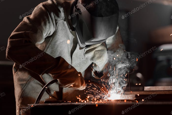 Worker in Protection Mask Welding Metal at Factory