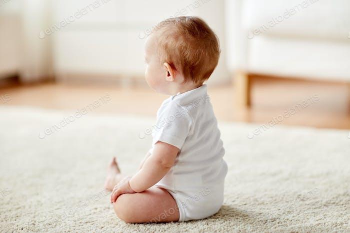 glücklich Baby Junge oder Mädchen sitzen auf dem Boden zu Hause