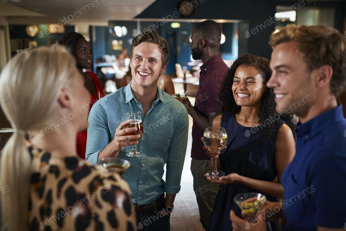 Group Of Young Friends Relaxing In Bar Together On Night Out
