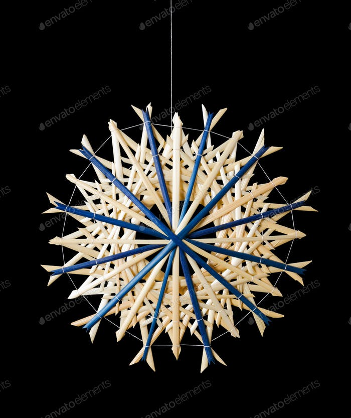 Blue straw star Christmas decoration over black
